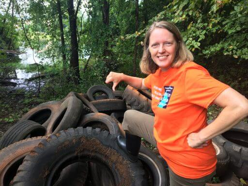 River Steward Kathy Urffer poses with a heap of tires cleaned out the river - no thanks!