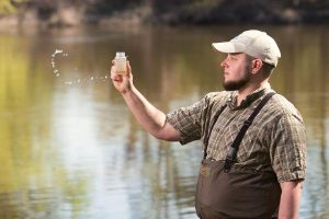 Water Quality Program Manager Ryan O'Donnell collects a water sample